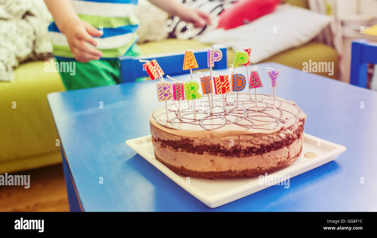 Birthday Party With Chocolate Cake Candles In Form Of Letters Young Boy Moving Around Blue Wooden Table Happy Birthda