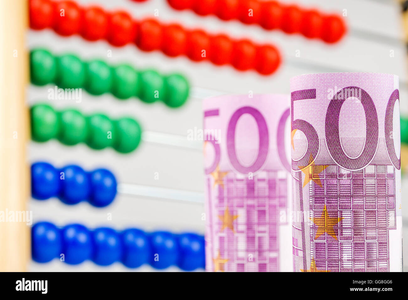 big euro banknotes with big wooden counter in the background as a school equipment and help for children Stock Photo