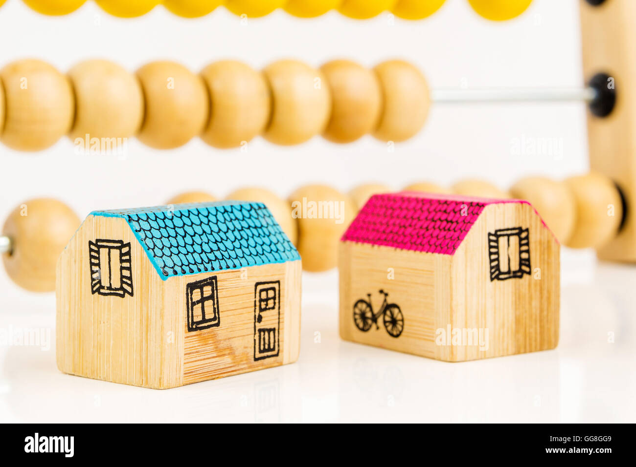 two miniatures of wooden houses with big wooden counter in the background as a school equipment and help for children, - Stock Image