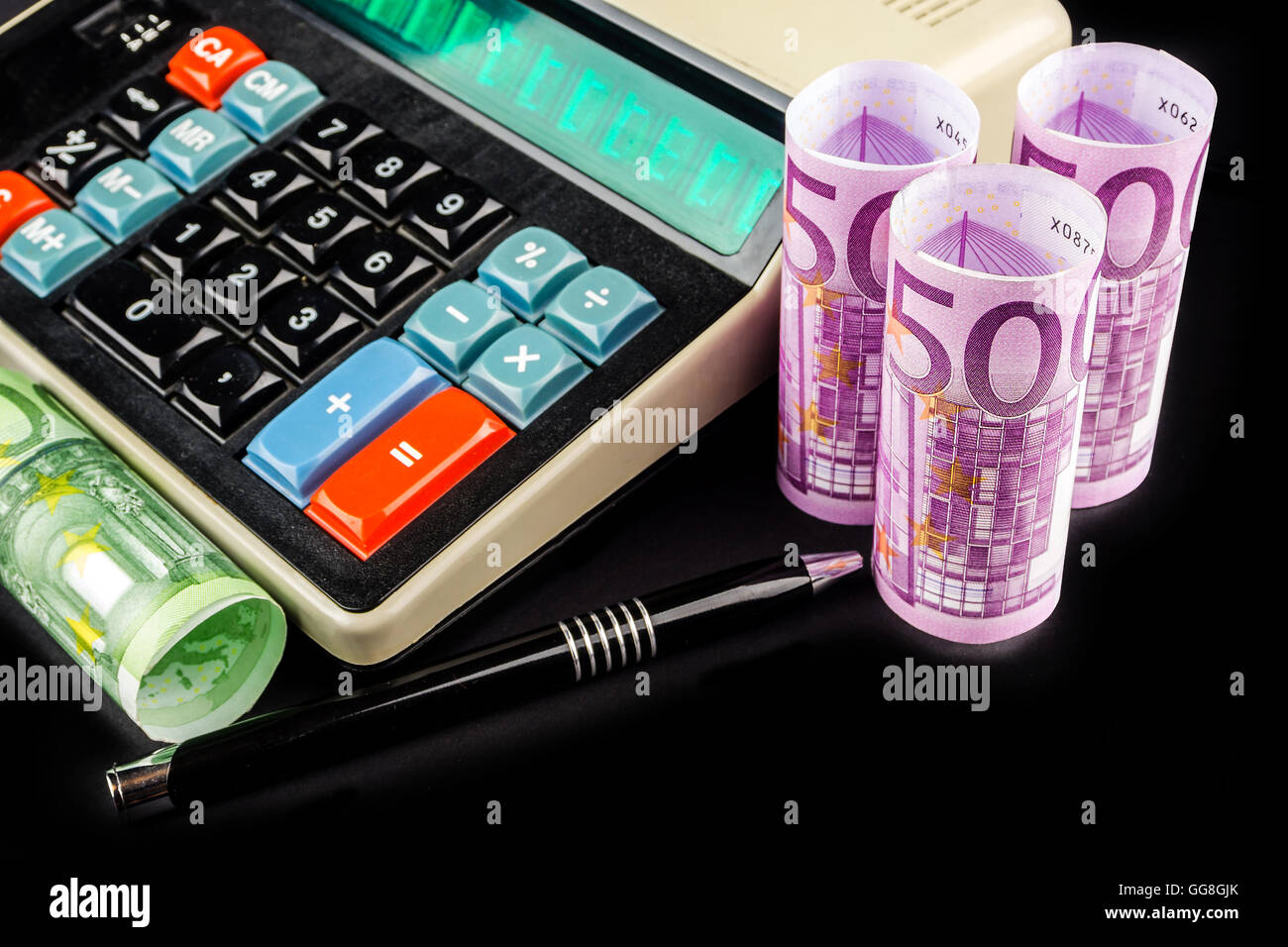 retro style calculator with a pen and big euro banknotes on black background - Stock Image