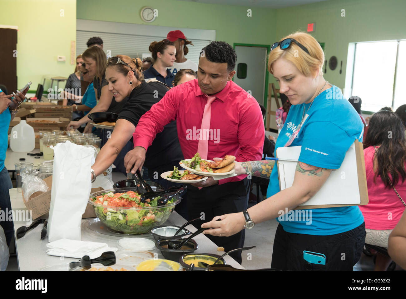 Adult volunteers serve themselves salad in cafeteria during after-school activity at middle school in Austin, Texas - Stock Image