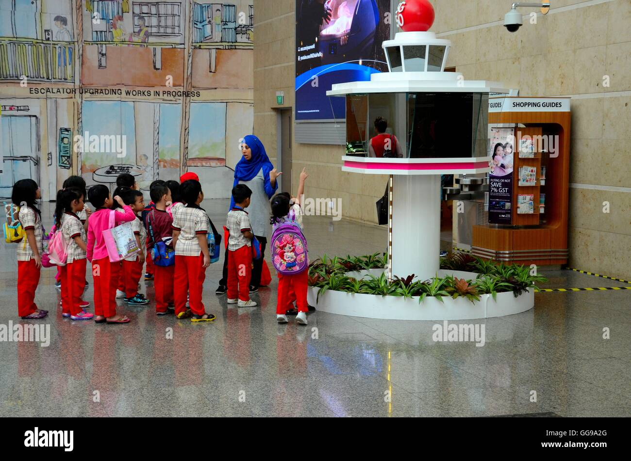 Schoolchildren on field trip listen to teacher wearing hijab at Changi airport model control tower Singapore - Stock Image