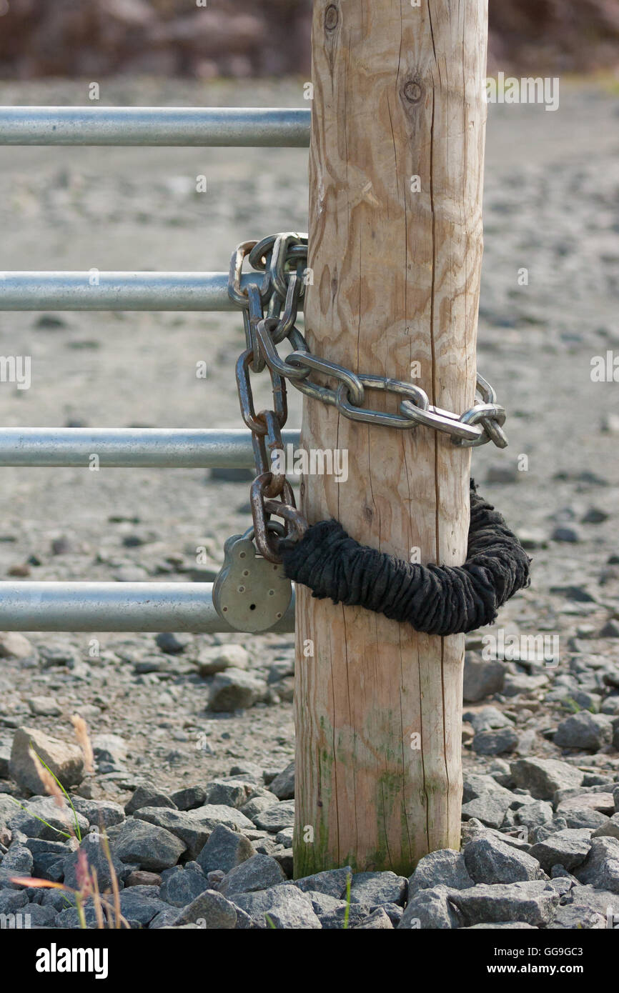 secure lock and chain on wooden post - Stock Image