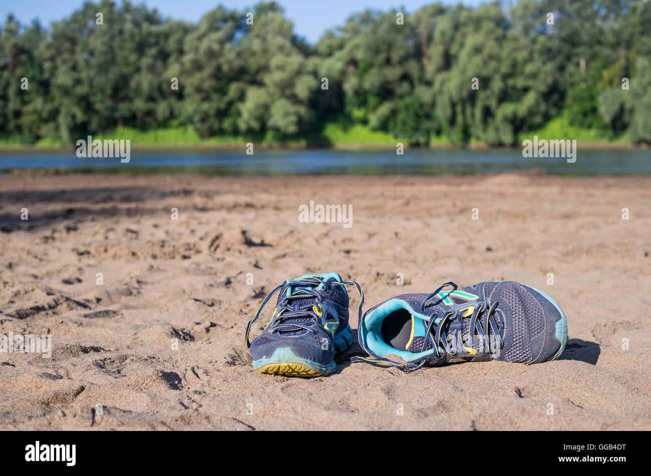 Running shoes lying on the sandy beach. Stock Photo