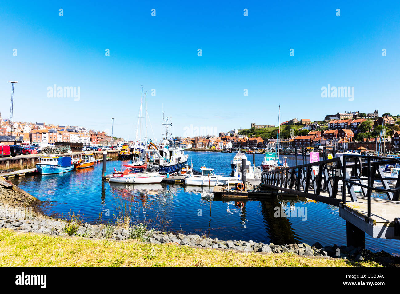 Fishing boats Whitby Town North Yorkshire Coast UK England moored in harbour harbor homes overlooking sea towns - Stock Image