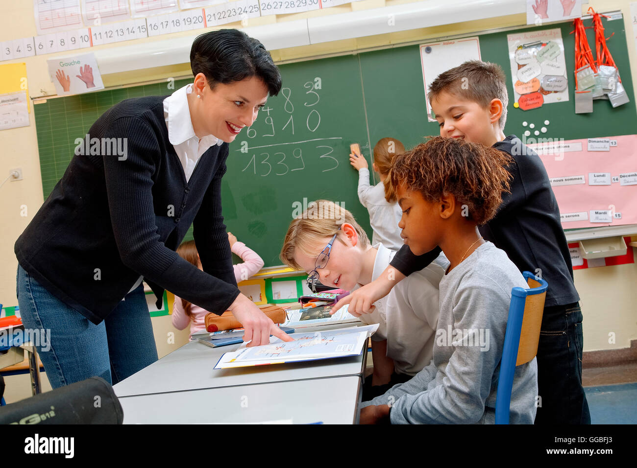 Portrait of diligent schoolkids and their teacher talking at lesson - Stock Image