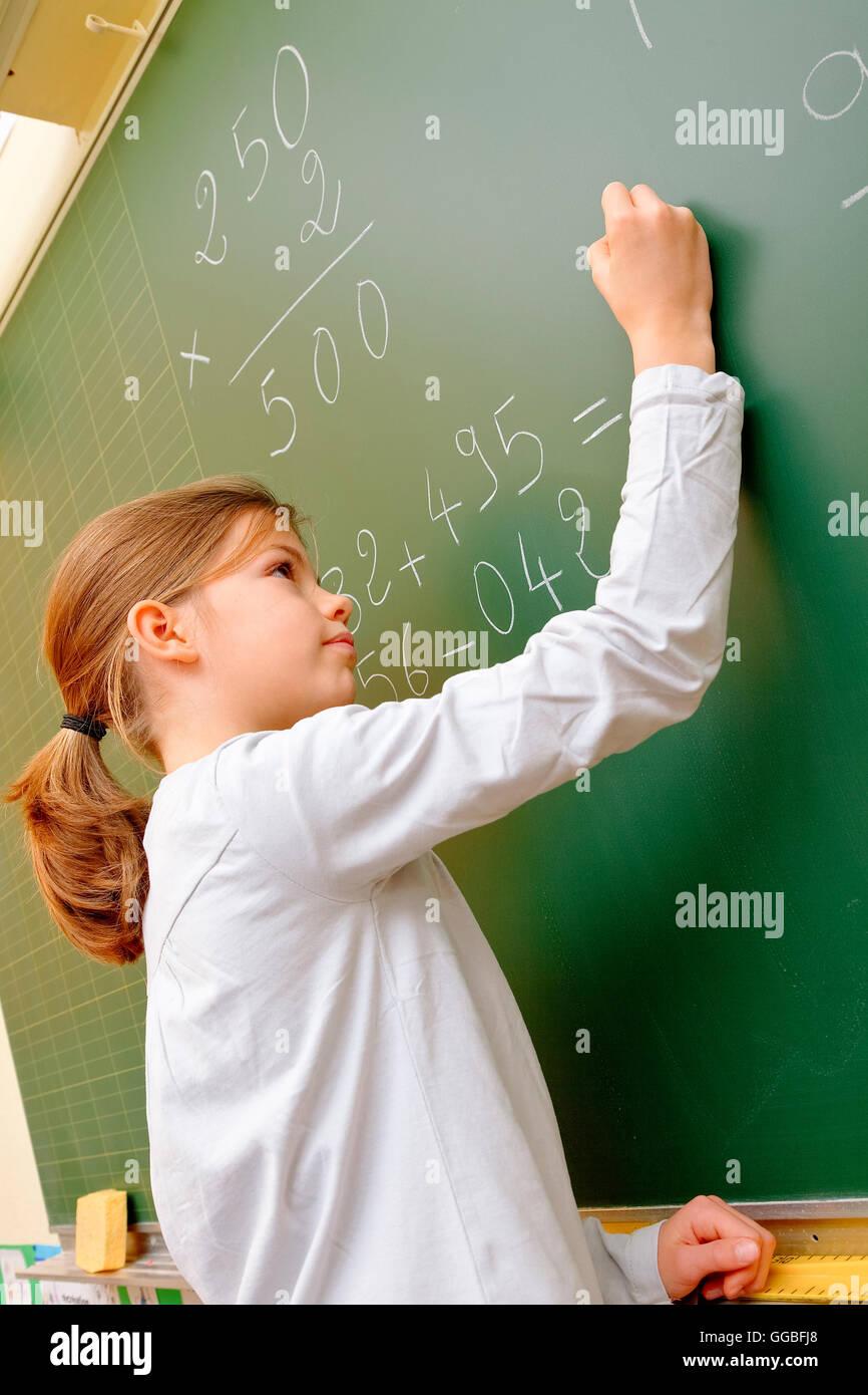 School girl writing on blackboard - Stock Image