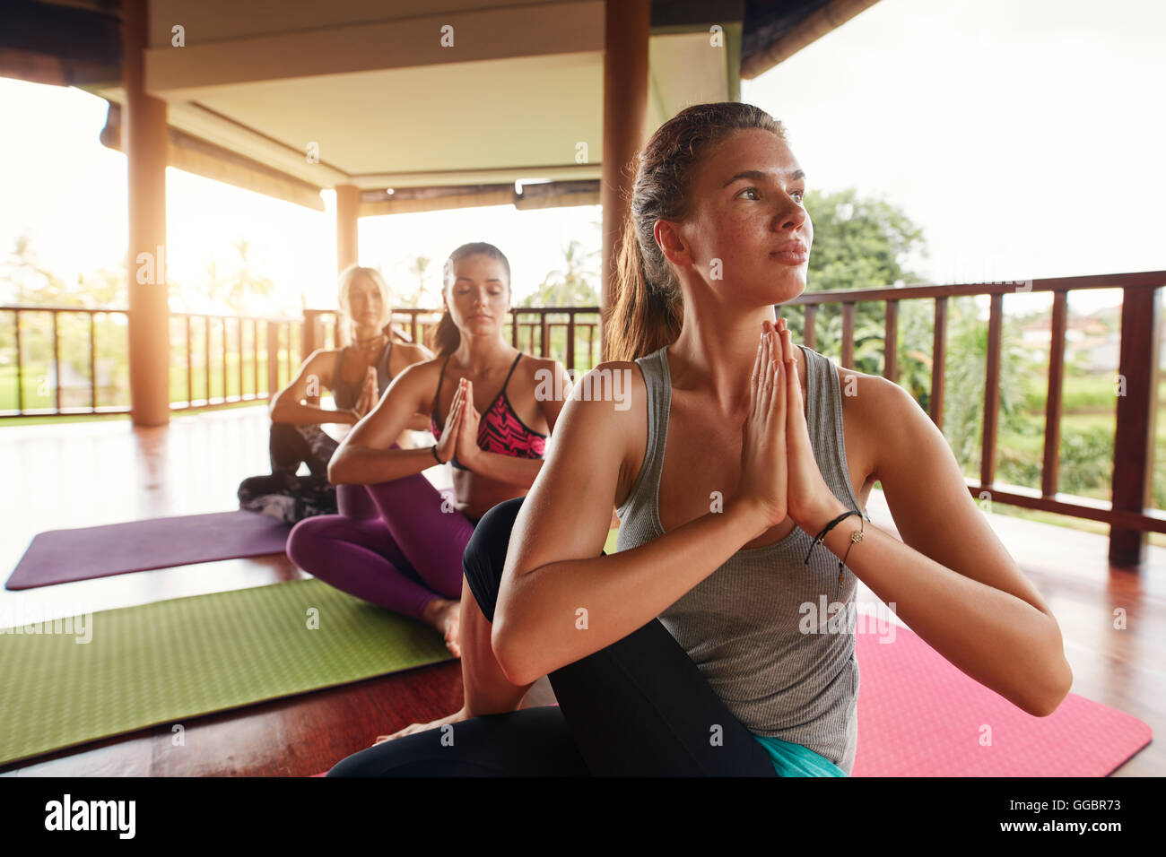 Shot of young woman practicing yoga in half spinal twist pose with their hands joined. Young people in yoga class doing yoga wor Stock Photo