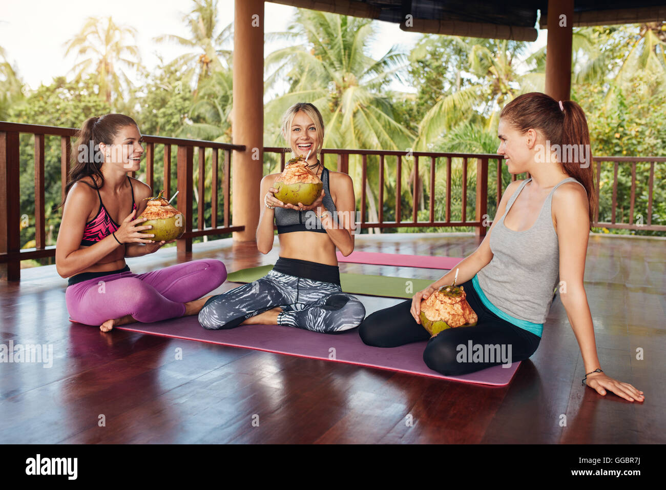Group of women relaxing with coconut juice after yoga class. Female friends during yoga class break at health club. - Stock Image