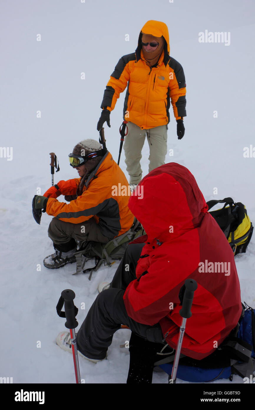 Geared up Climbers resting  on snow fields on route up - Mera Peak High camp - bad weather - Stock Image