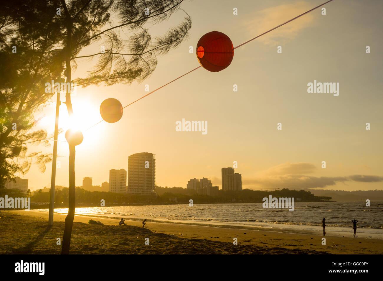 Setting sun over the city of Kota Kinabalu, Sabah, Malaysia Borneo, showing the beach and city skyline. - Stock Image
