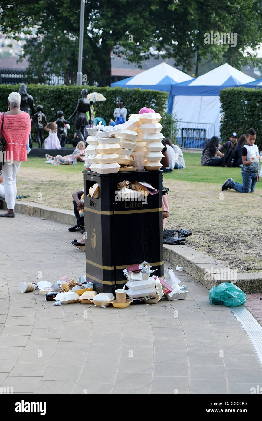 A street side public rubbish bin full to capacity and overflowing with fast food containers Stock Photo