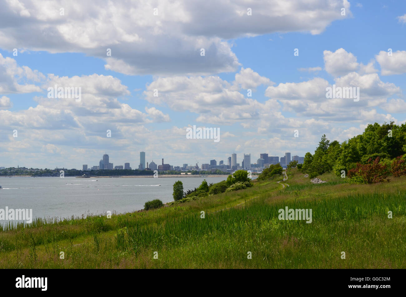 Cityscape of Boston with puffy white clouds over Boston from the harbor. - Stock Image