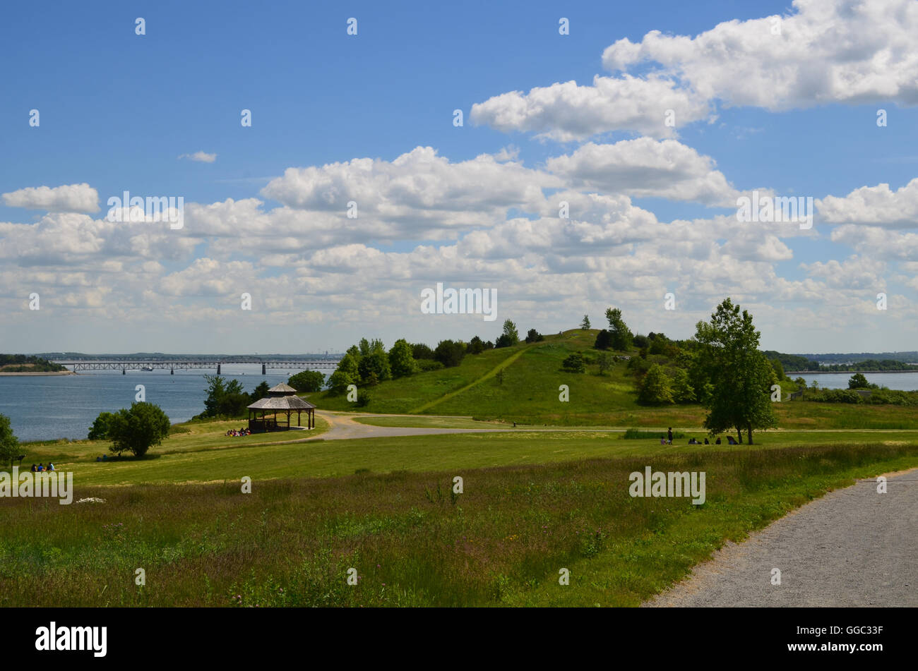 Lush Spectacle Island  with fluffy clouds and green grass. - Stock Image