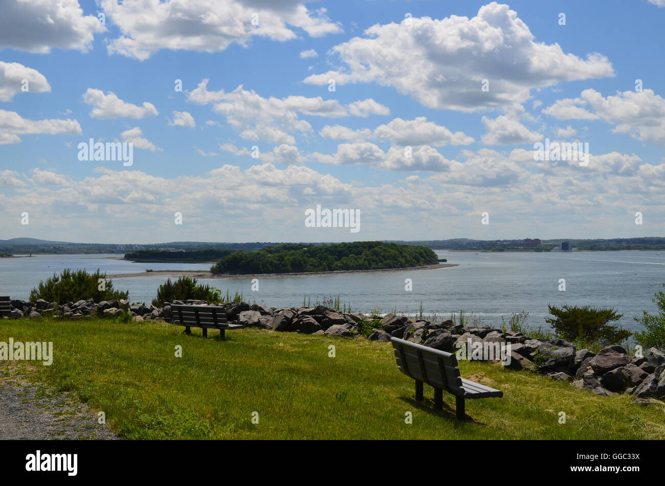 Benches facing Boston Harbor on Spectacle Island. - Stock Image