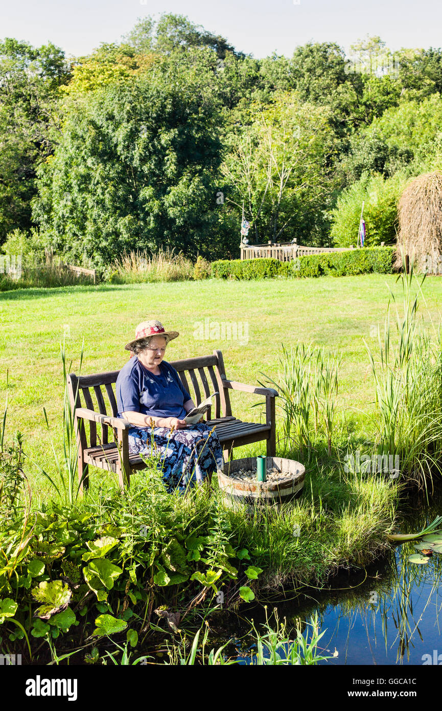 Lady sitting reading in a quiet garden setting - Stock Image