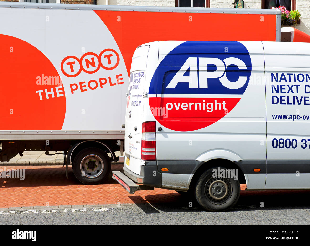 Two delivery vans - TNT and APC - parked together, England UK - Stock Image