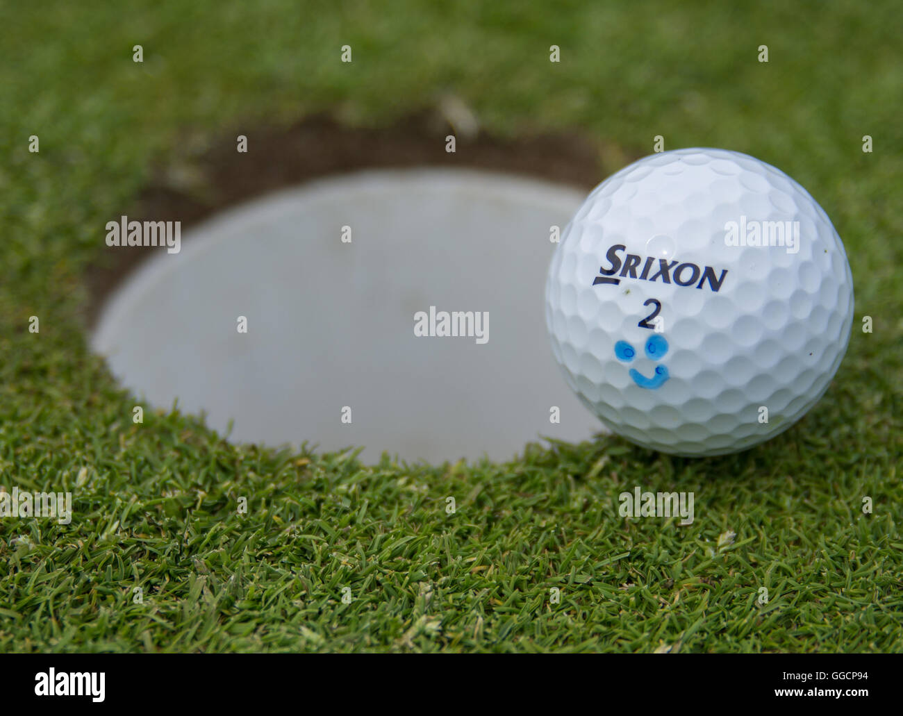 Srixon Golf Ball resting besides the hole (landscape) - Stock Image