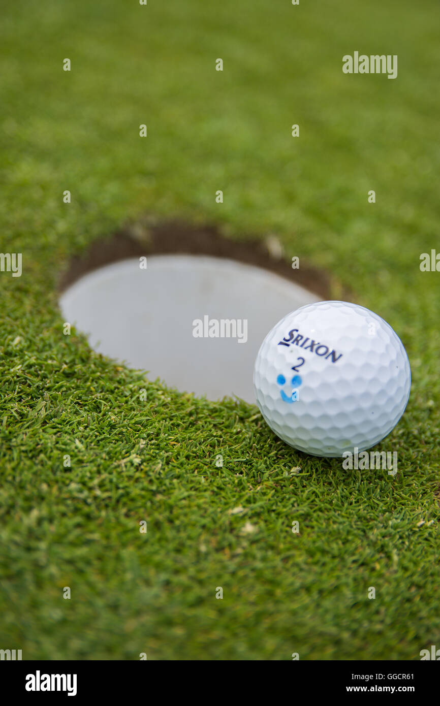 Srixon Golf Ball resting alongside the hole - Stock Image