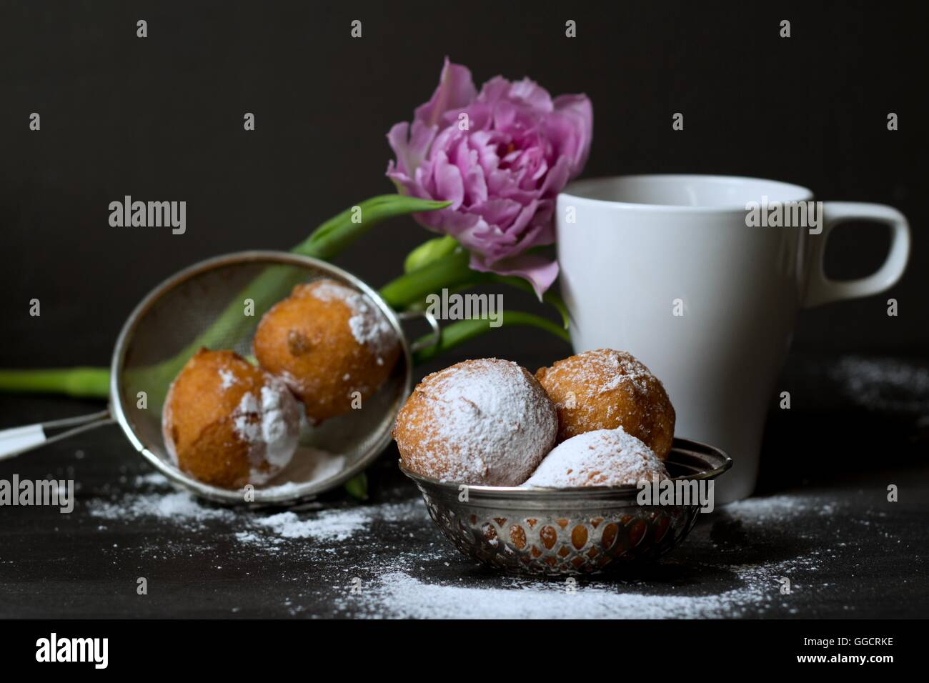 Jelly doughnuts, pink tulip and cup - Stock Image