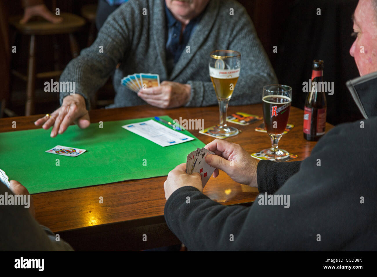 Elderly card players playing cards on table in pub - Stock Image