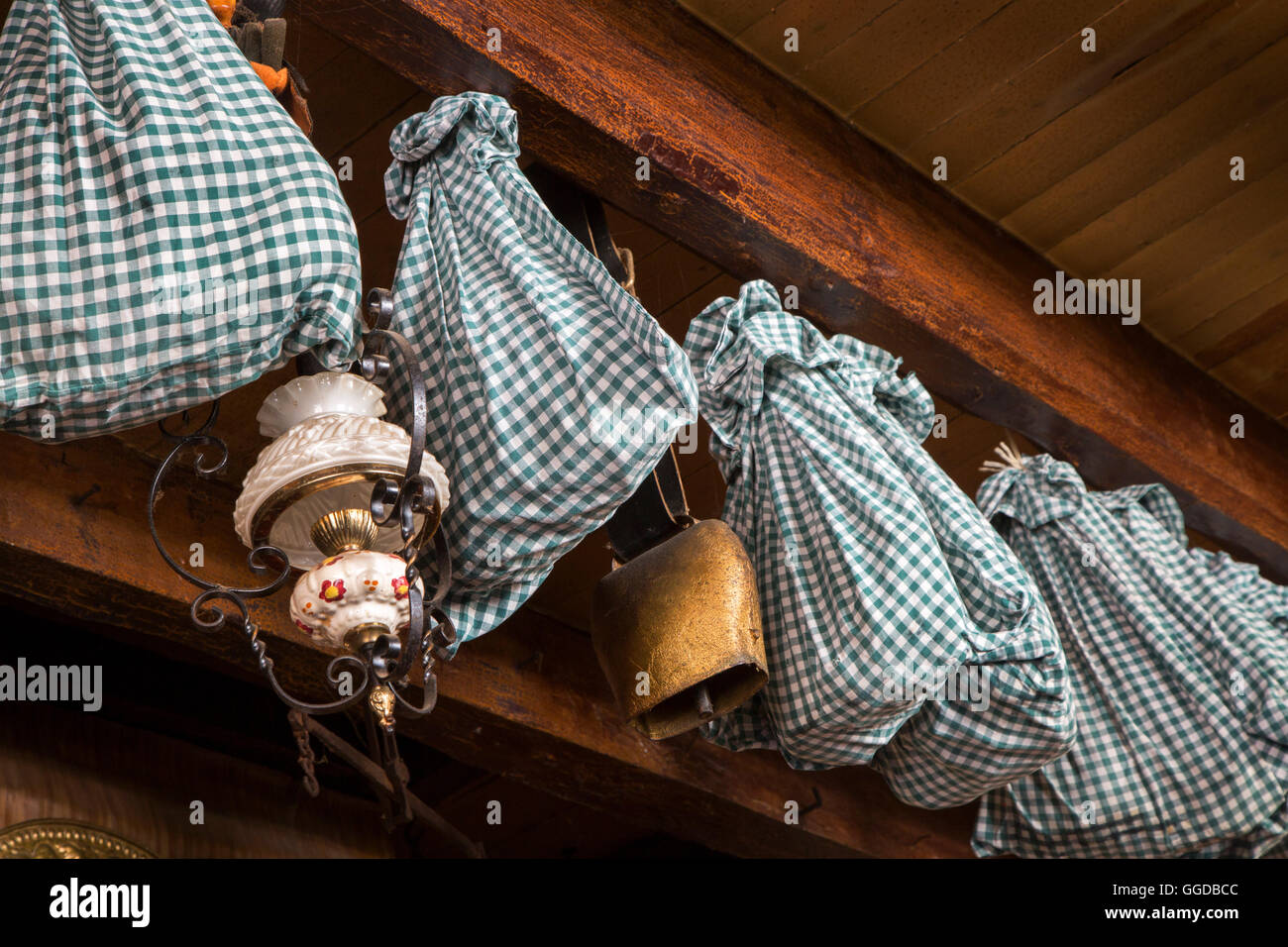 Hams wrapped in cloth for further aging and stored by hanging from the ceiling in farmhouse - Stock Image