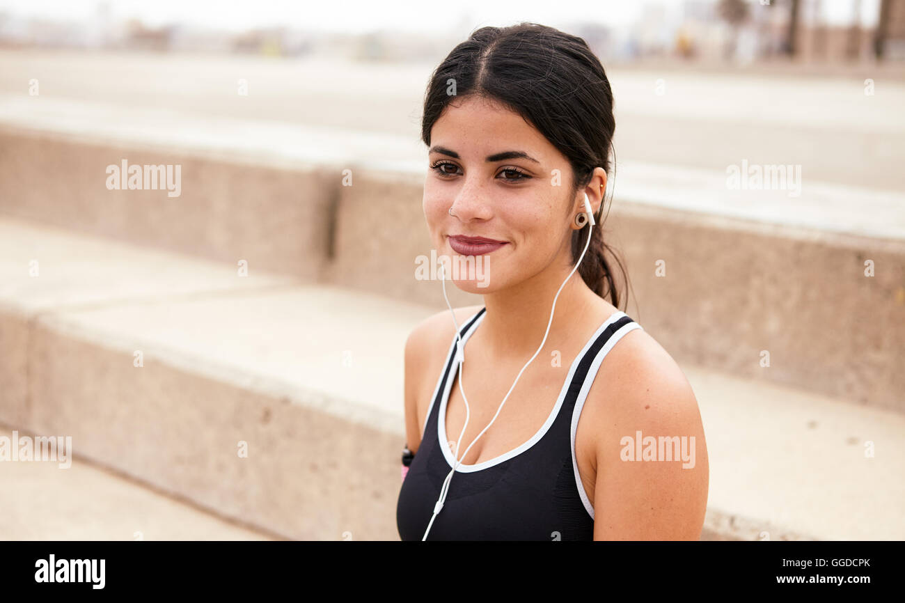 Young brunette with earphones smiling dreamily with steps behind her while wearing casual clothes and looking ahead - Stock Image