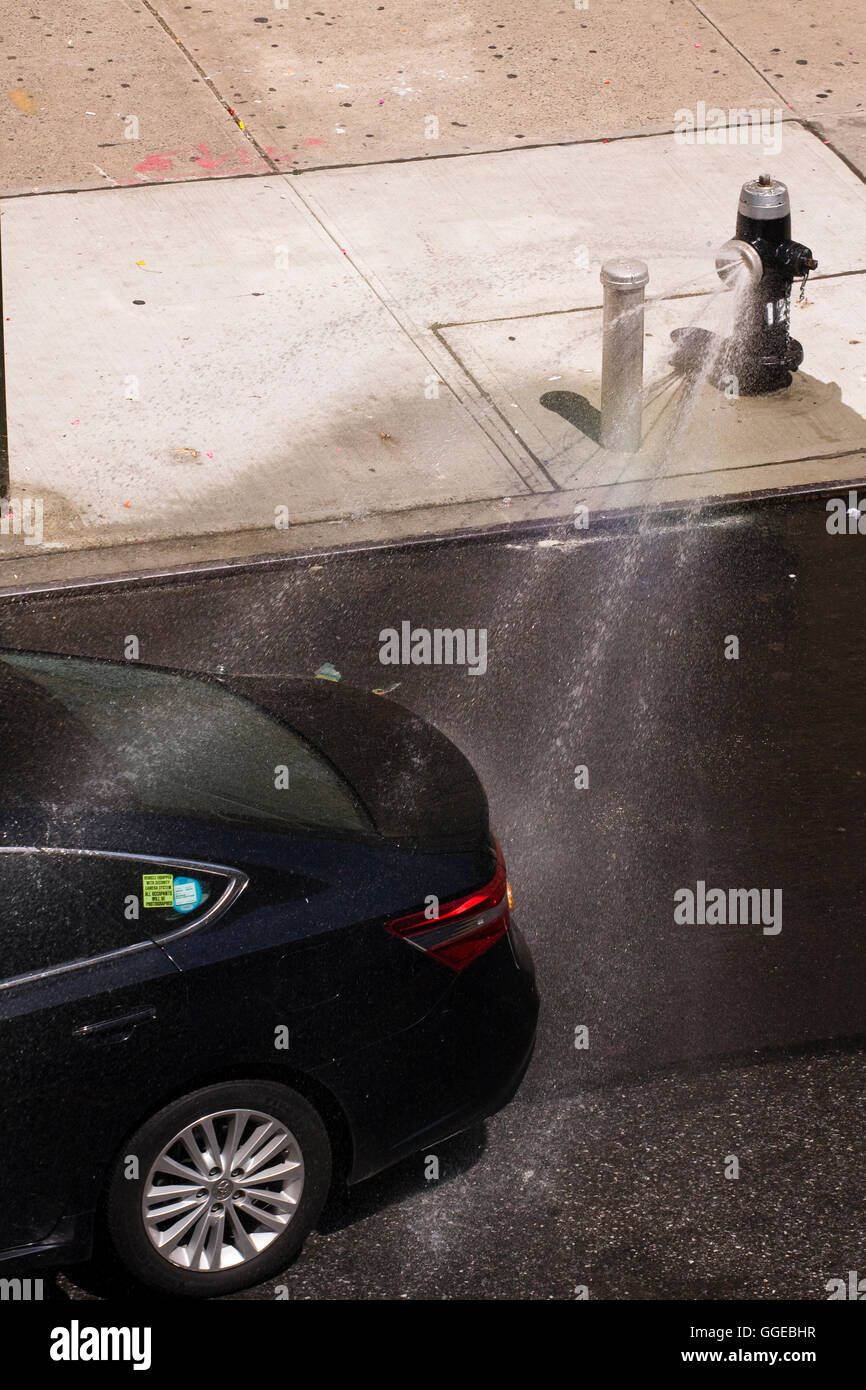 Dark colored Toyota automobile driving through streams of water from an open fire hydrant with a spray nozzle attached - Stock Image