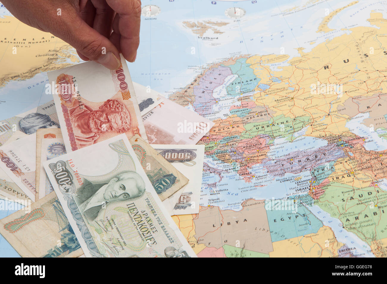 greek drachmas and euro banknote with a hand selection on a europe map - Stock Image