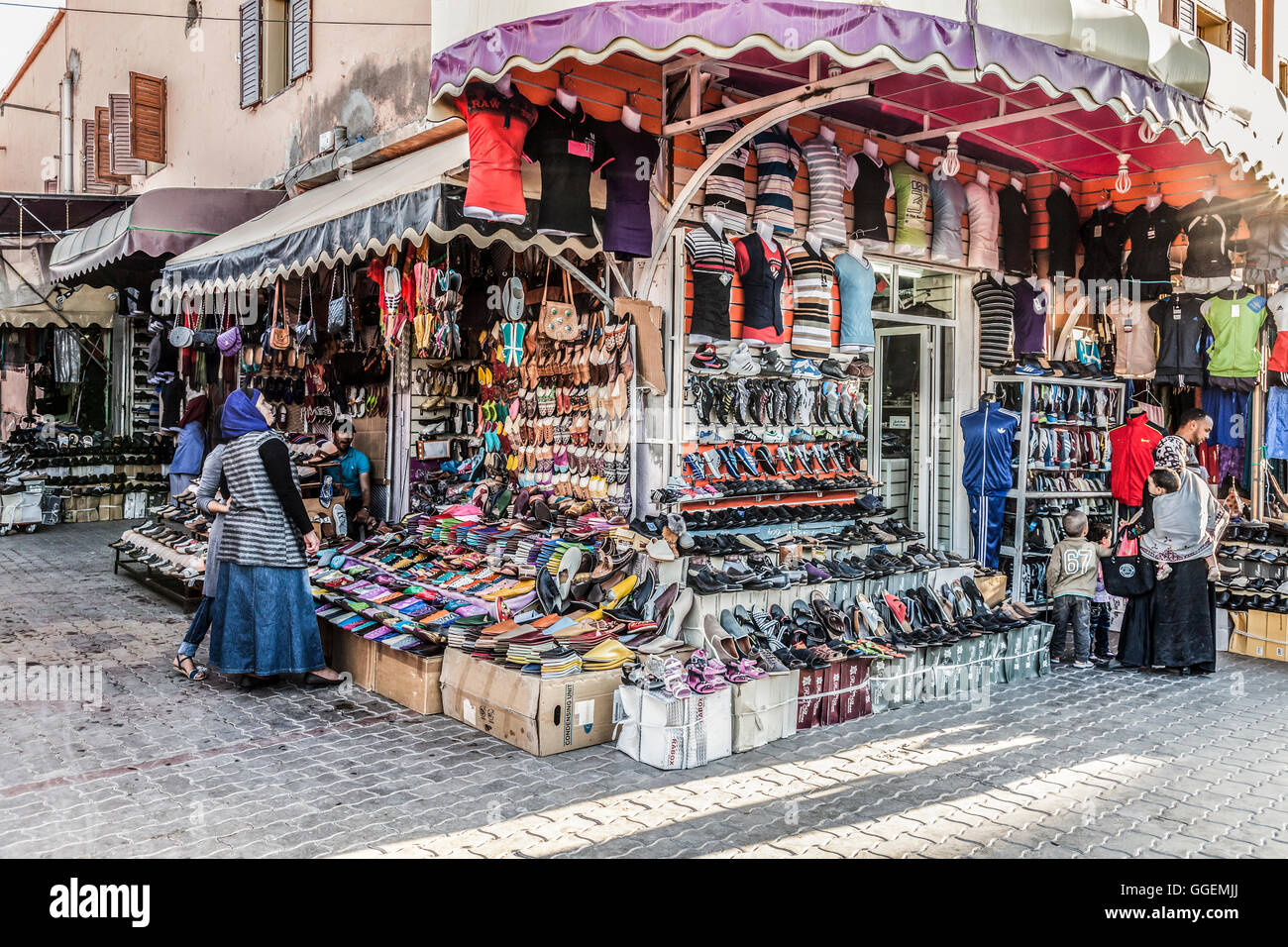 Vendor & shoppers at a linked group of stalls selling shoes, bags and sports clothes in a sreet in downtown - Stock Image
