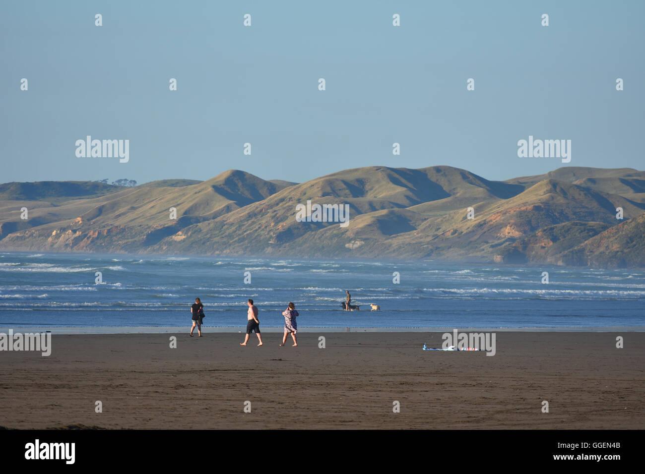 people NZ beach sea Raglan coast - Stock Image