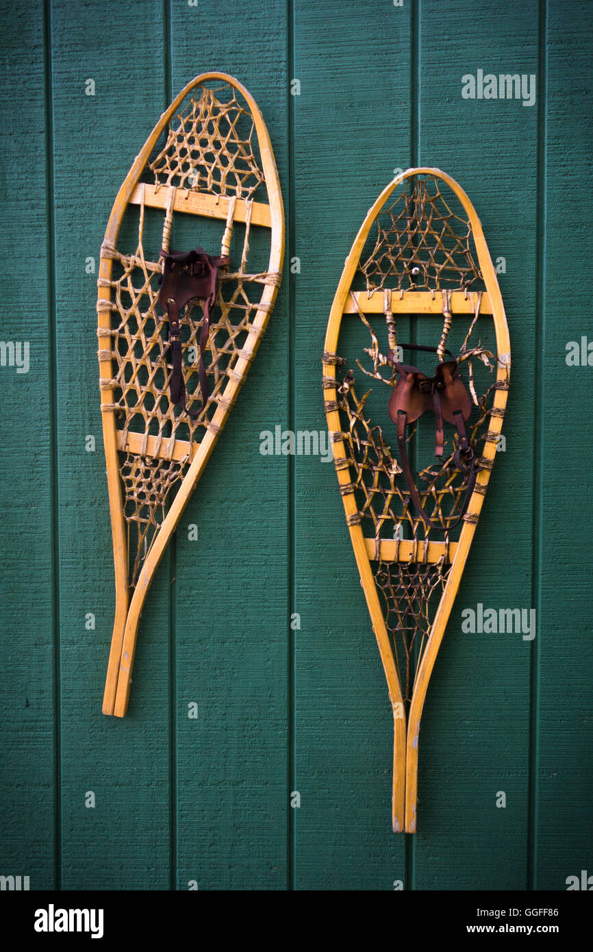 A pair of traditional teardrop snowshoes mounted on a green wooden wall - Stock Image