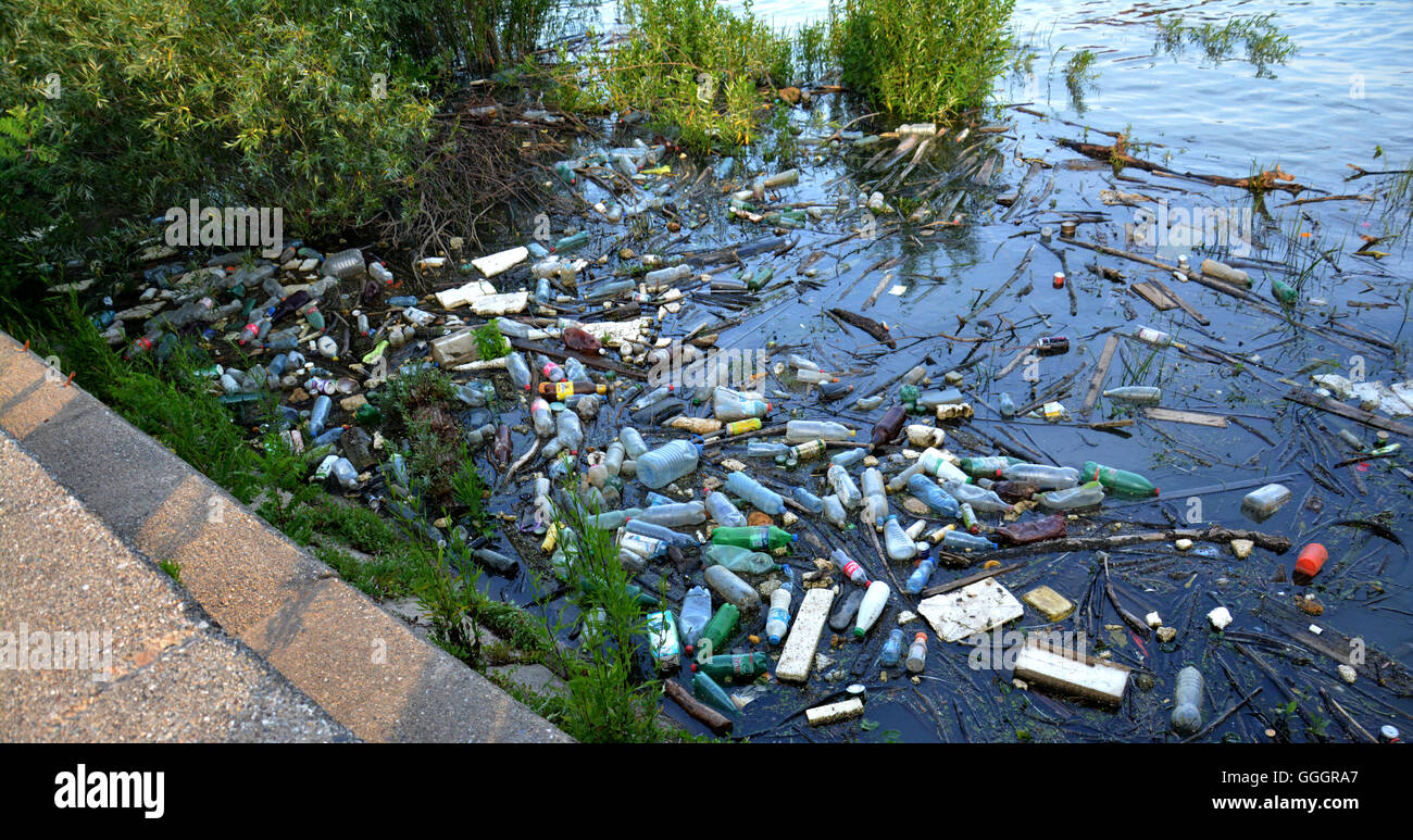 Polluted river with various garbage and trash - Stock Image