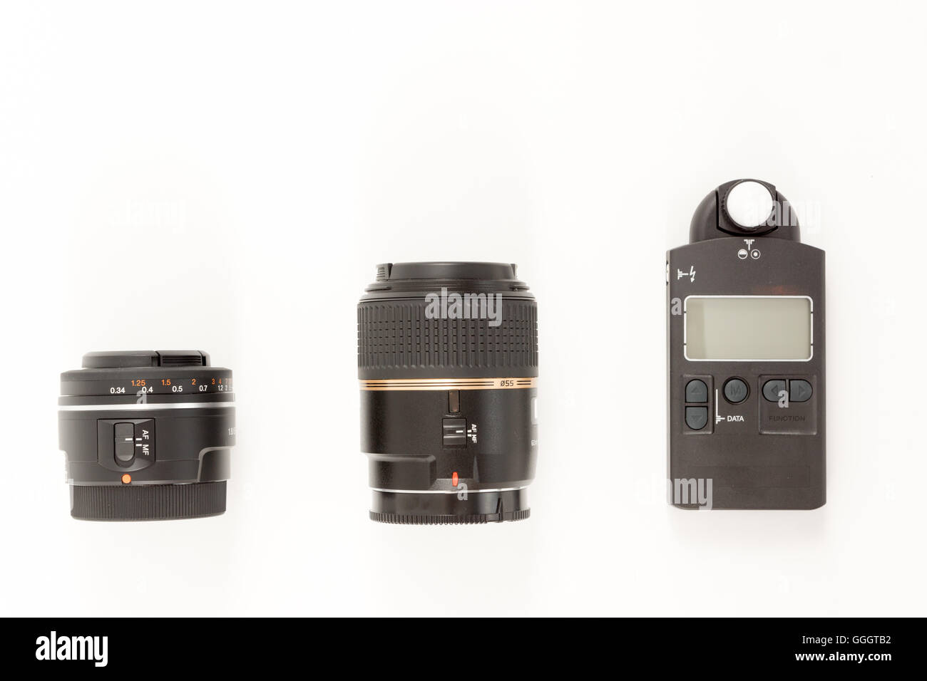 Lenses and light meter on white background Stock Photo