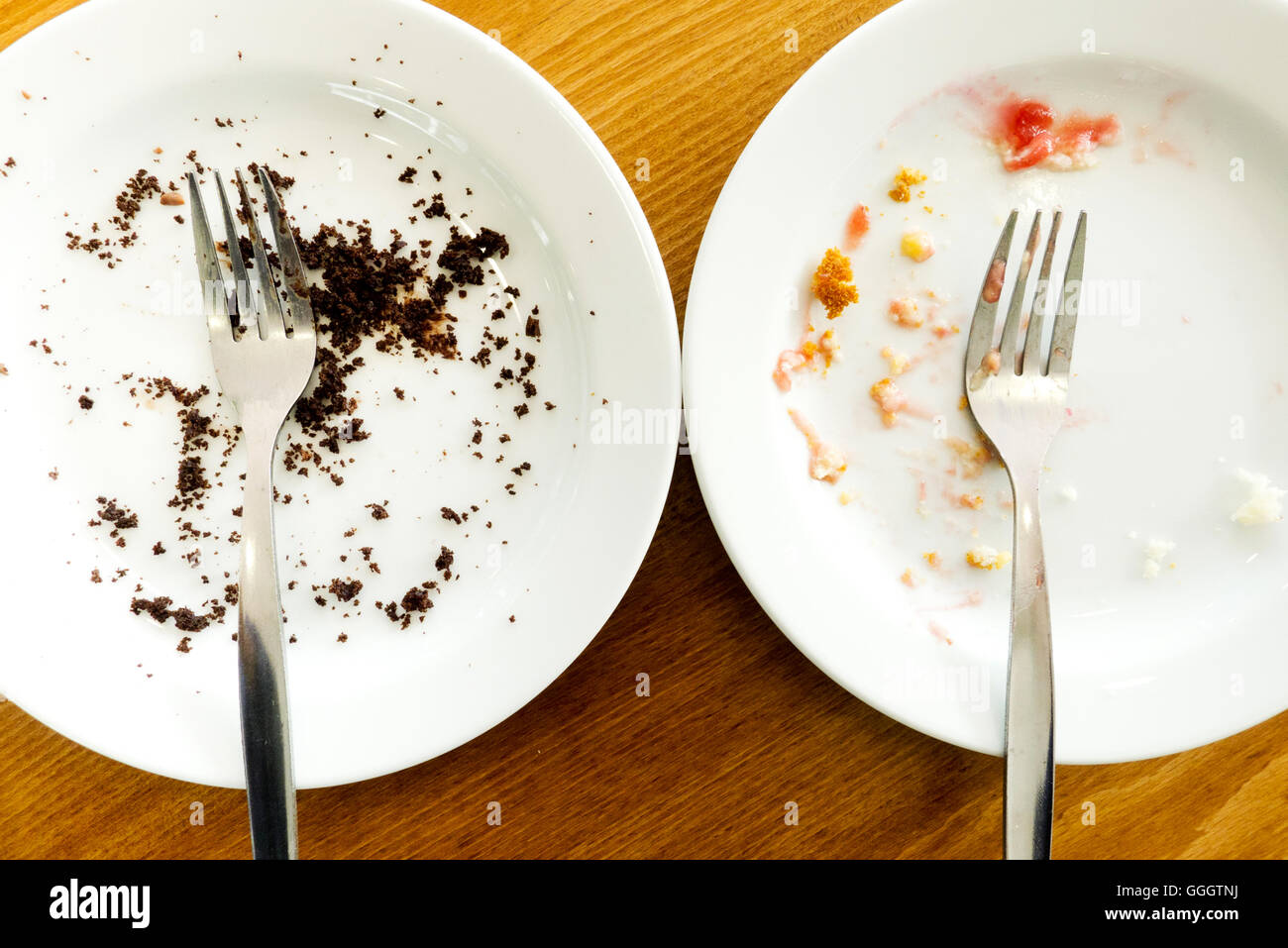 two white plates with forks and crumbs - Stock Image