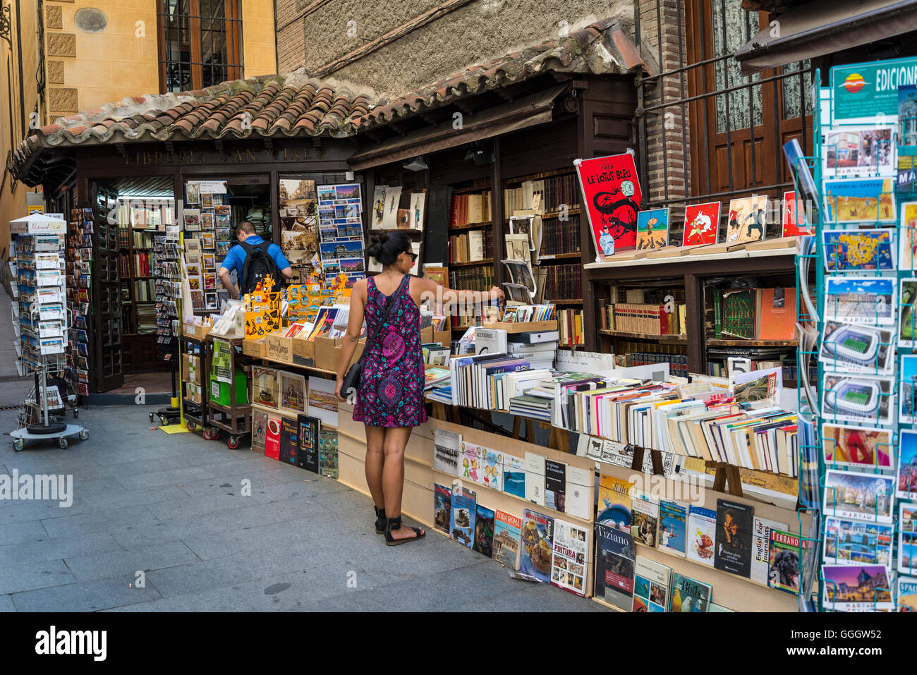 Woman browsing in secondhand bookshop in Pasadizo de San Gines, Calle de Arenal, Madrid, Spain - Stock Image