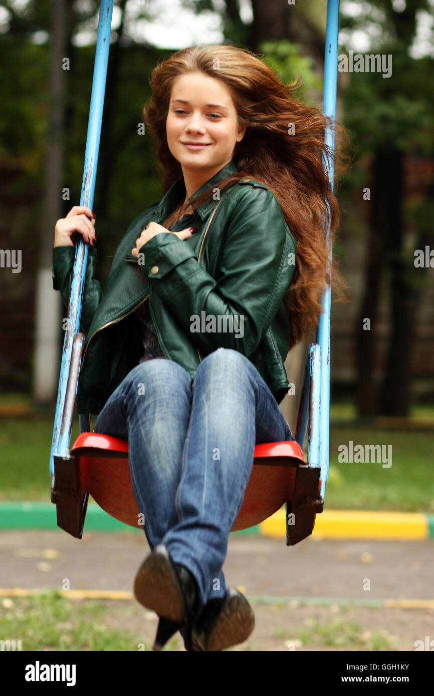 Young woman wearing sitting on a swing in a park - Stock Image