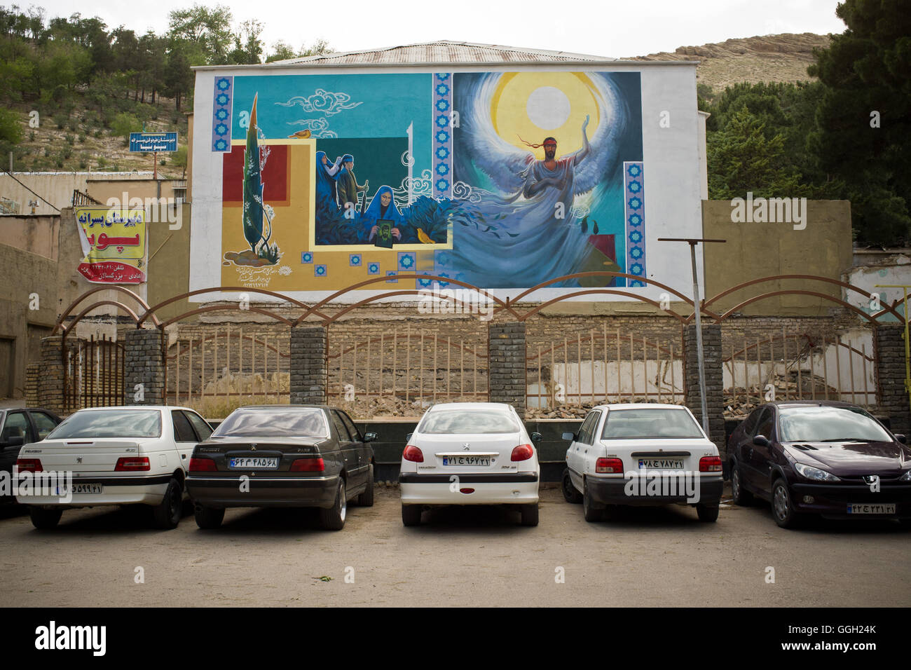 Cars parked in front of a mural of the martyrs of the Iranian revolution in Khorramabad, Iran. © Jordi Boixareu - Stock Image