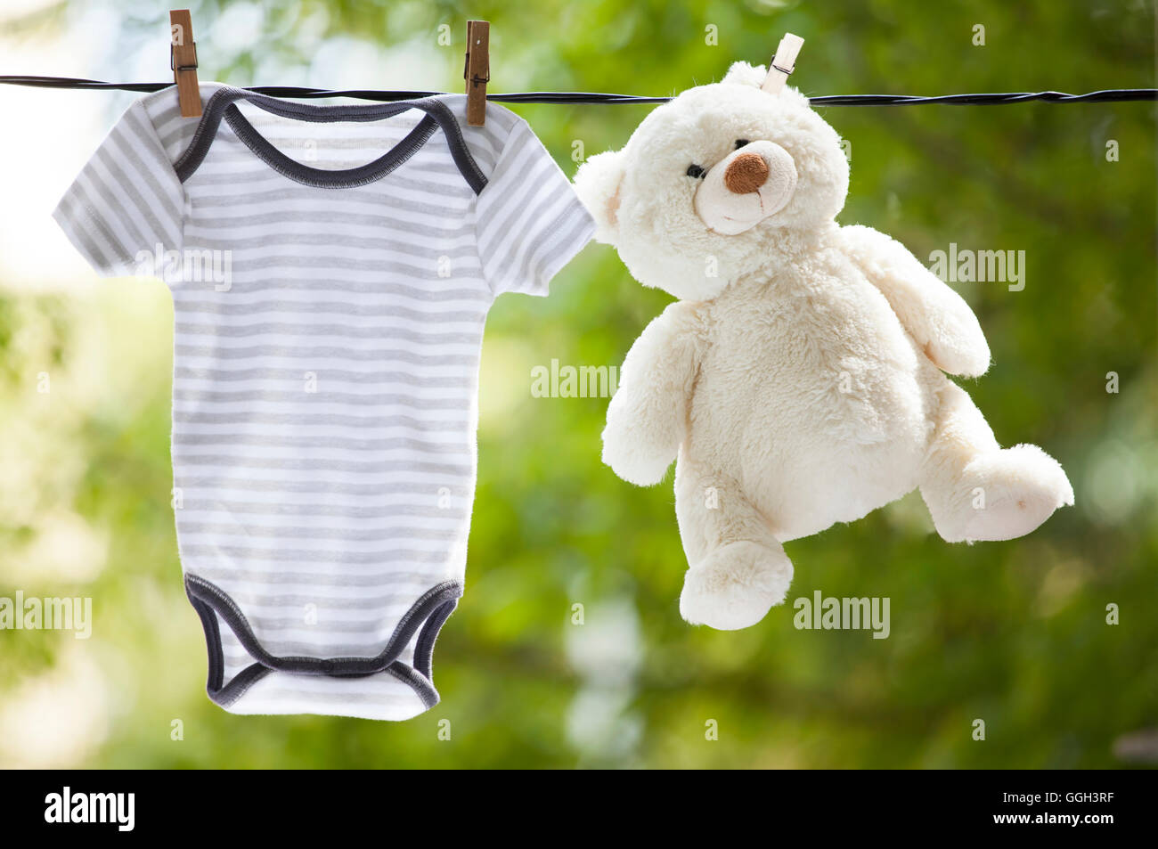 Baby clothes and teddy bear hanging on the clothesline - family concept - Stock Image