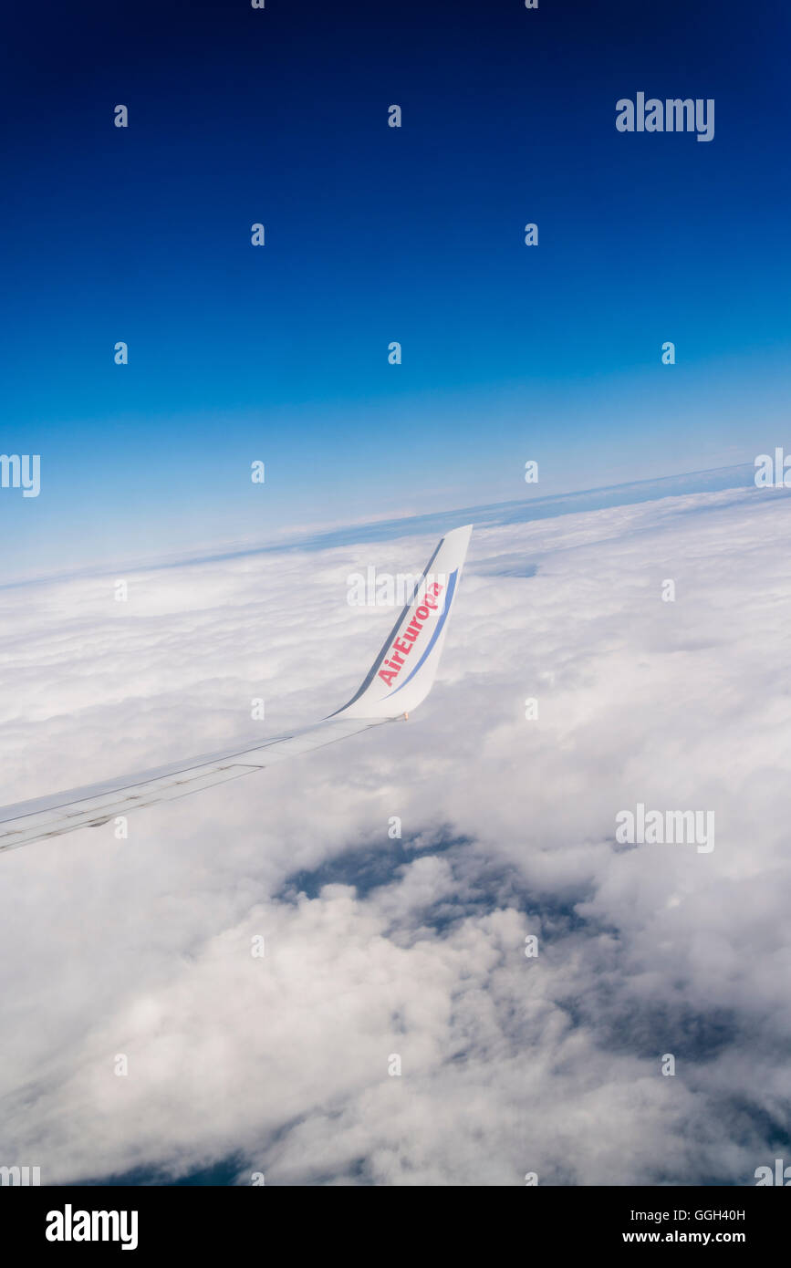 Air Europa wing flying above clouds - Stock Image