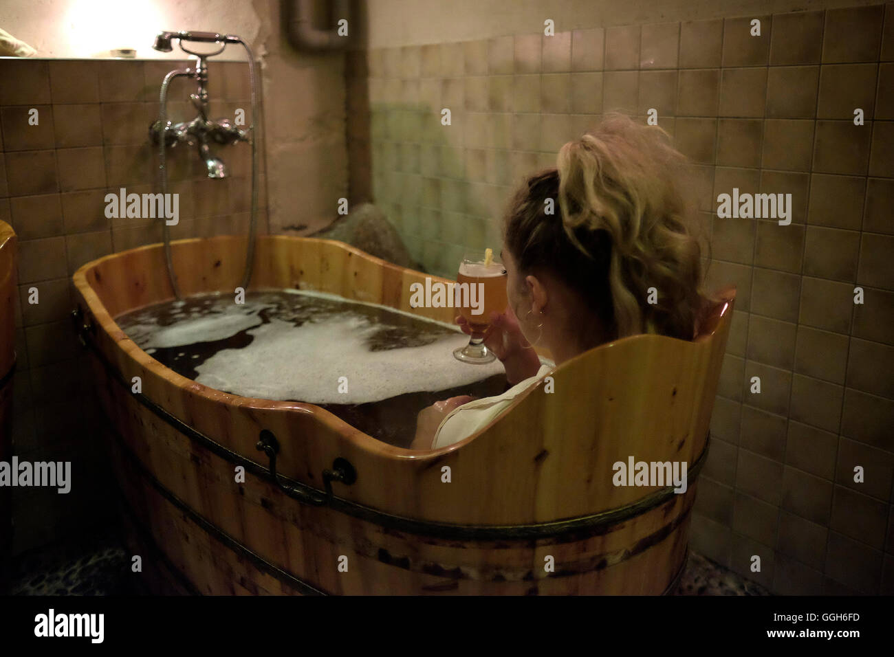 Bernadita a young Lithuanian woman soaking in a tub filled of beer in the spa of Hotel Romantic in the town of Panevezys - Stock Image