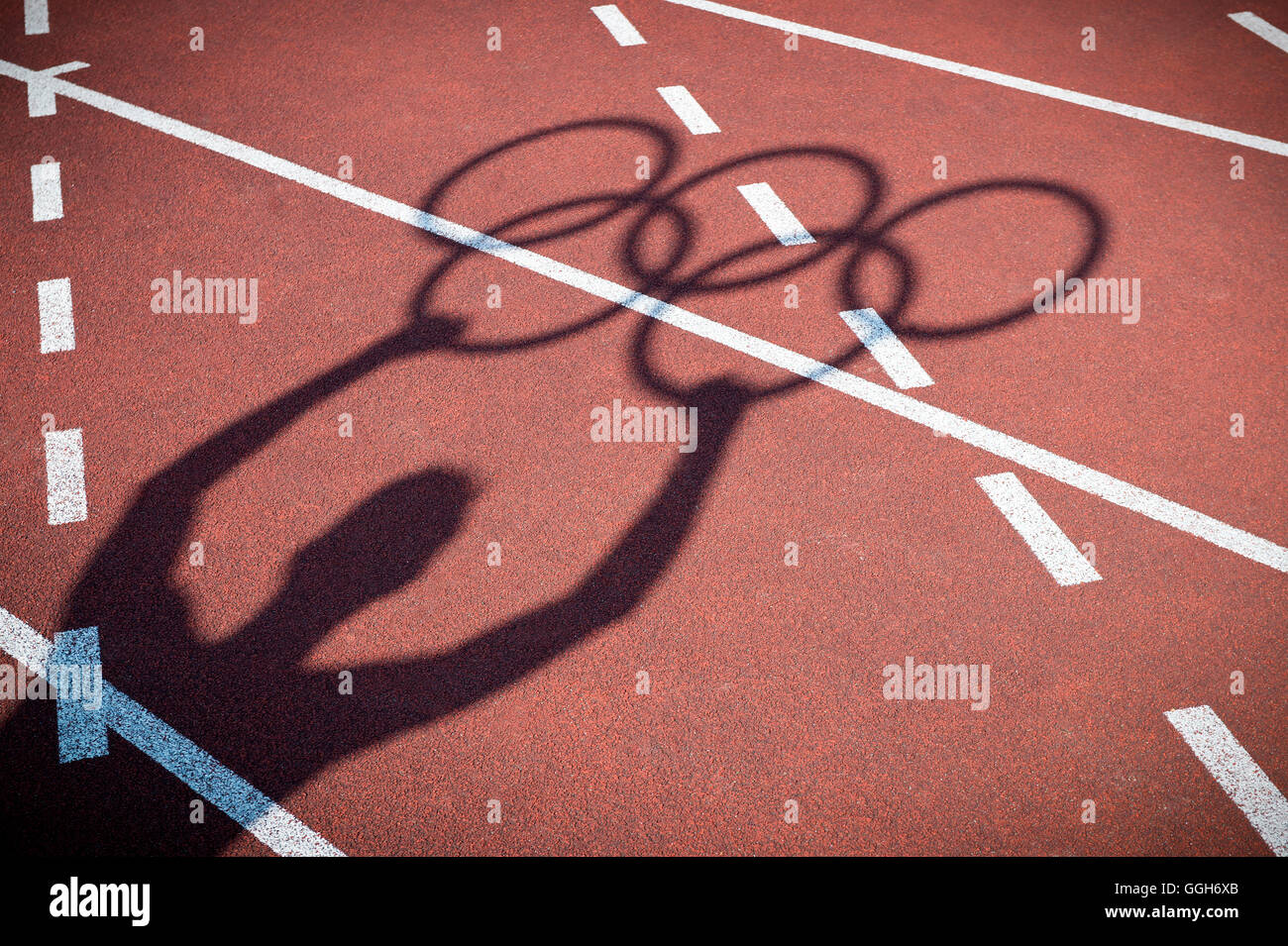 RIO DE JANEIRO - FEBRUARY 12, 2015: Shadow of an athlete holds Olympic rings on the lanes of a red running track. Stock Photo