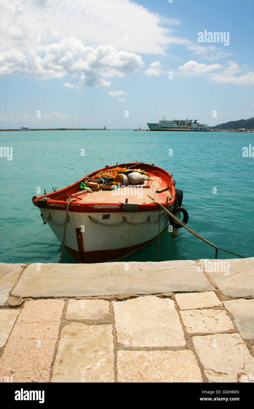 Moored rowing boat in the harbor of Zankinthos, on the island of Zante, Greece, with flagged stone pathway Stock Photo