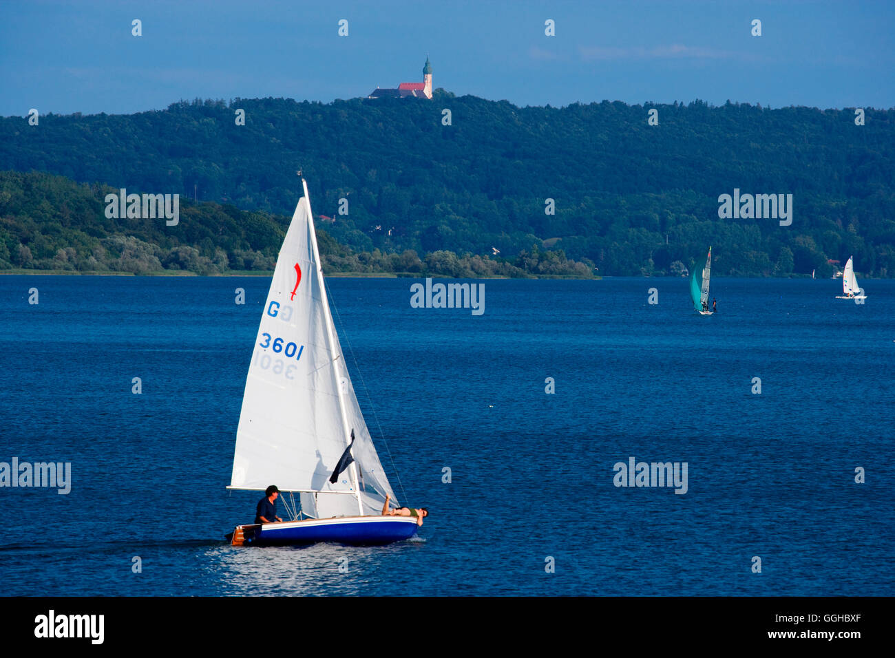 Sailing boat and Andechs monastery in the background, Ammersee, Upper Bavaria, Bavaria, Germany - Stock Image