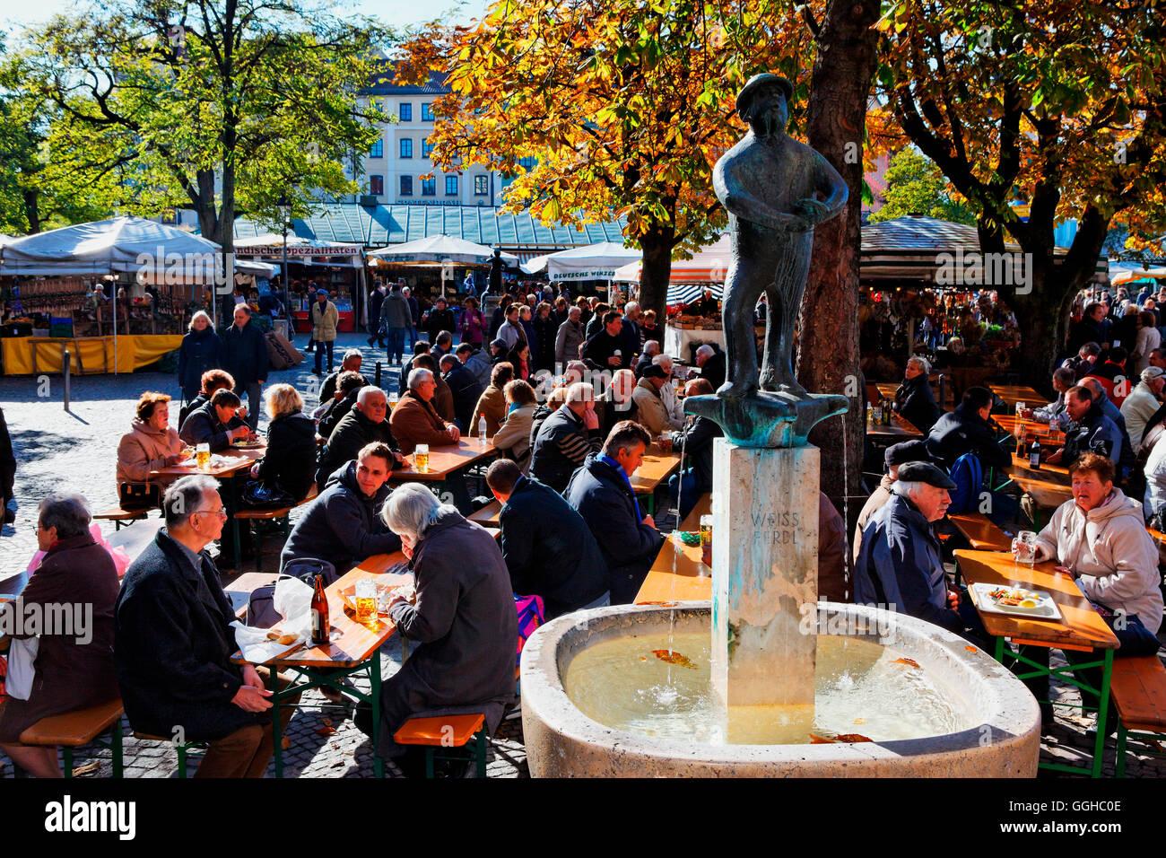 Beer garden and Weiss Ferdl Fountain at Viktualienmarkt, Munich, Upper Bavaria, Bavaria, Germany - Stock Image