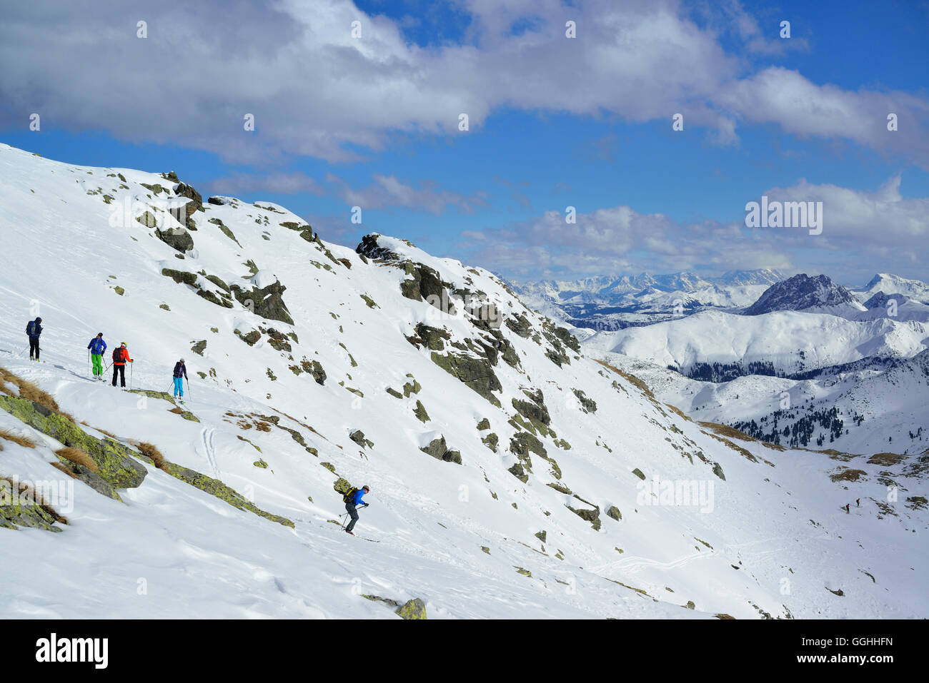 Back-country skiers downhill skiing from Schafsiedel, Kitzbuehel Alps, Tyrol, Austria - Stock Image