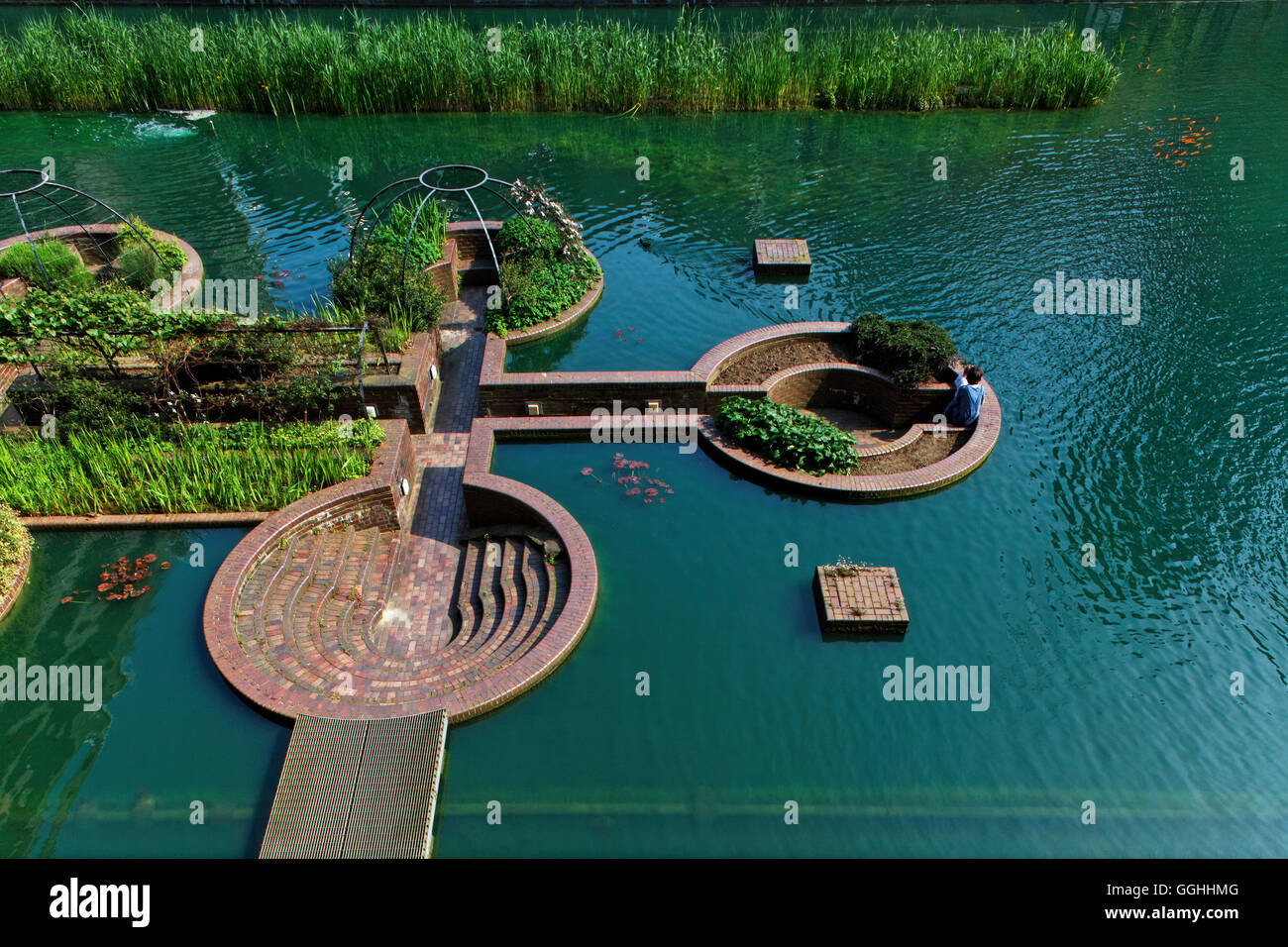 Garden with sitting areas below water level in the Barbican centre, London, England, United Kingdom - Stock Image