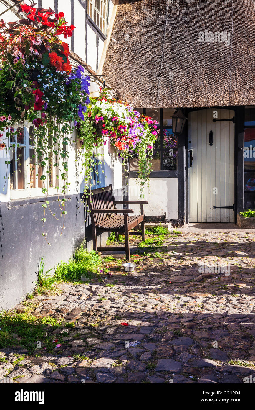 Thatched cottage with hanging baskets. - Stock Image