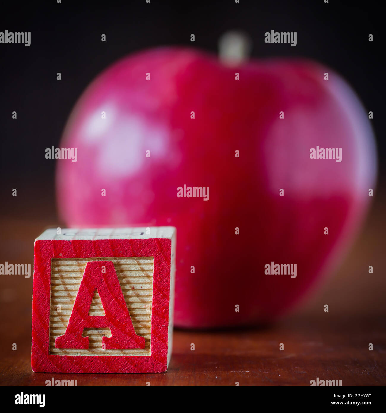 A child's wooden block with the letter A and an apple defocused in the background. - Stock Image