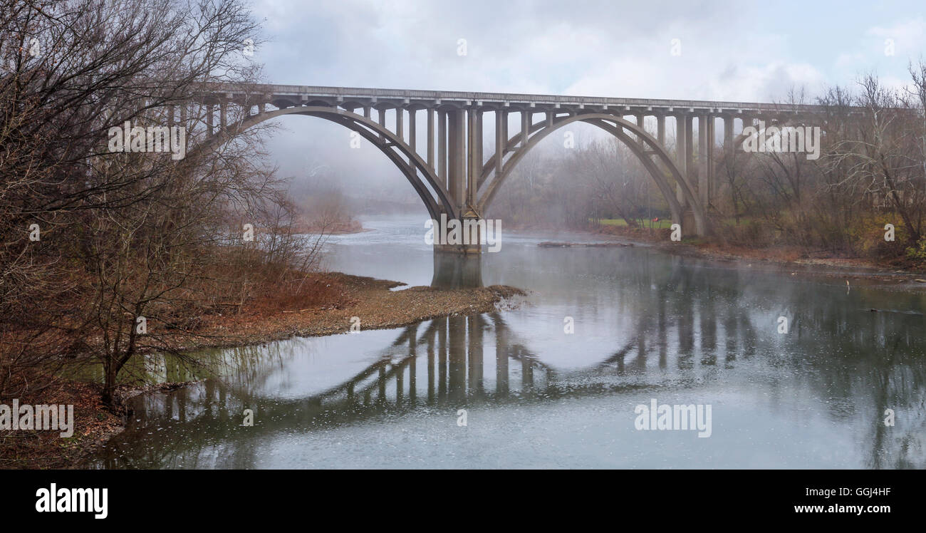 A Symmetrical Reflection, A Roadway Bridge on a Misty Late Autumn Morning Over The Little Miami River in Southwestern - Stock Image
